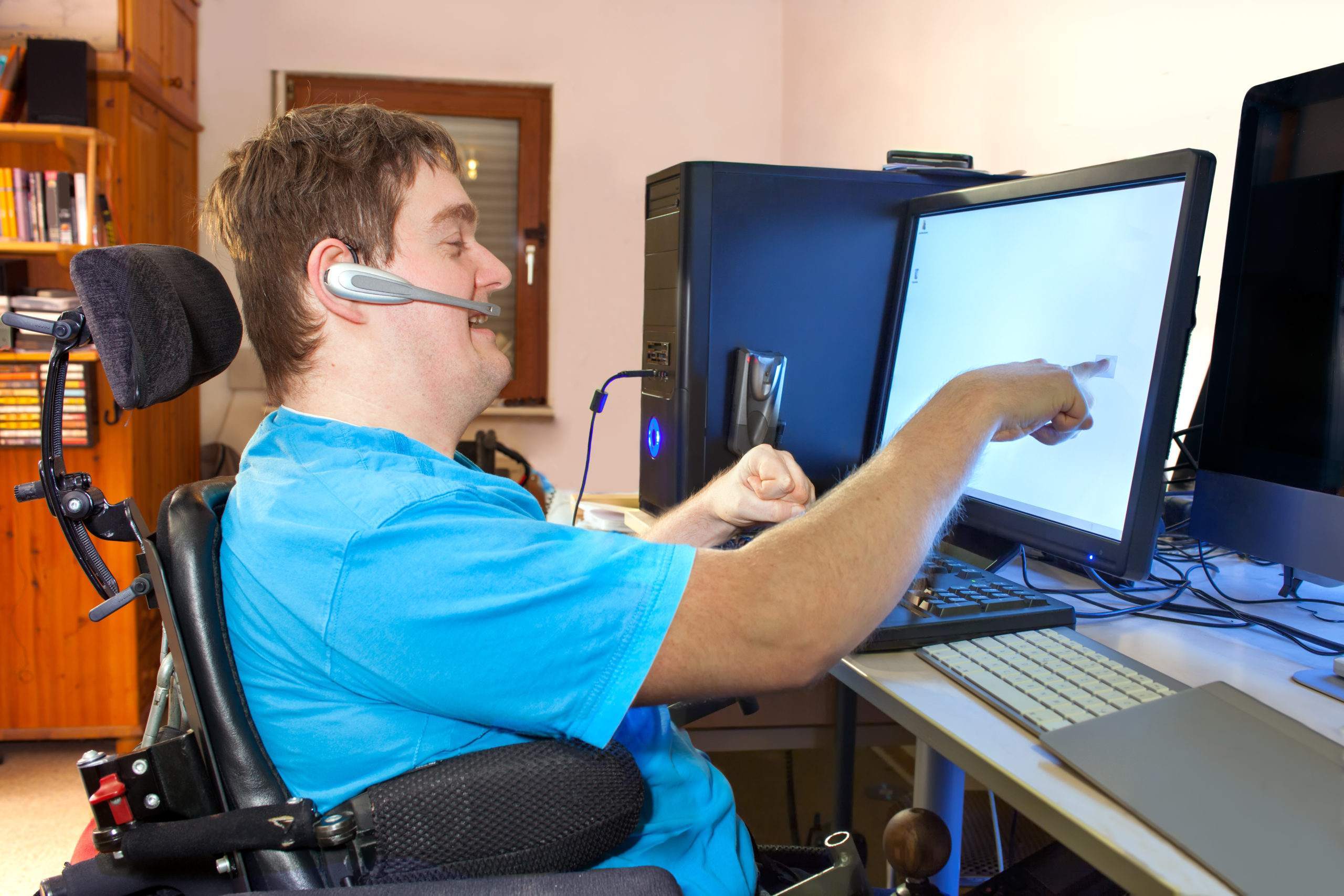 Image of a man with cerebral palsy in a wheelchair using adaptive technology on a computer. The man is wearing a blue tshirt and a bluetooth headset, and is smiling